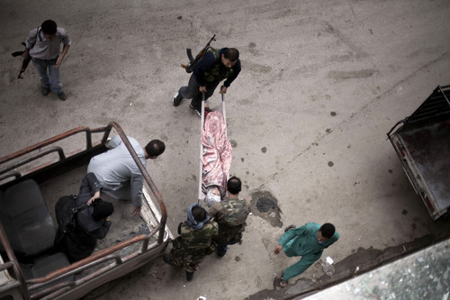 In this Thursday, Oct. 11, 2012 photo, Free Syrian Army fighters take a wounded Syrian woman to Dar al-Shifa hospital, Aleppo, Syria. (AP Photo/Manu Brabo)