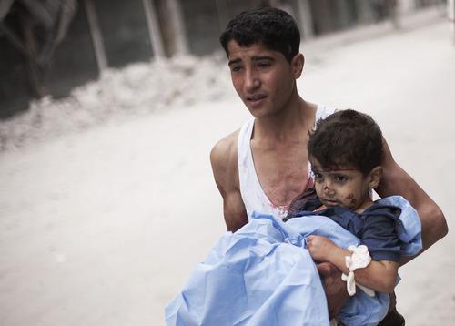 RETRANSMISSION FOR ALTERNATIVE CROP - A Syrian youth holds a child wounded by Syrian Army shelling near Dar El Shifa hospital in Aleppo, Syria, Thursday, Oct. 11, 2012. (AP Photo/ Manu Brabo)