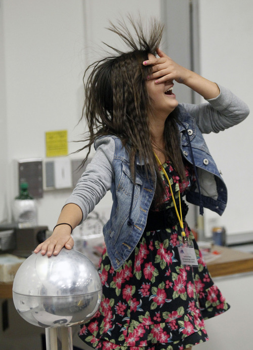 Al Hartmann  |  The Salt Lake Tribune Cottonwood High School student Sandia Kafley's hair stands on end during a physics static electricity experiment Friday given by University of Utah lecture demonstration specialist Adam Beehler during the 2nd annual Refugee Youth Conference that brought together more than 200 refugee students from Granite, Canyons and Salt Lake school districts to learn about the importance of education, particularly higher education.