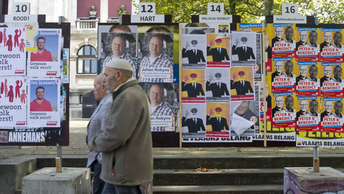 In this photo taken on Monday, Oct. 8, 2012, two men walk by election campaign posters in Antwerp, Belgium. Historic world port and hip fashionista capital, Antwerp has always lived on the crest of the wave. Now, a separatist Fleming is seeking to make the city his own on Sunday and use it as a base for breaking away from Belgium. Local elections will take place on Sunday, Oct. 14, 2012. (AP Photo/Virginia Mayo)