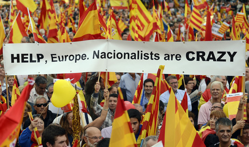 People opposed to the independence of the Catalonia region of Spain, hold Catalan and Spanish flags during the holiday known as Dia de la Hispanidad, Spain's National Day in Barcelona, Spain, Friday, Oct. 12, 2012. Spain is in recession and under pressure to fix its finances while celebrating the day Christopher Columbus discovered America in the name of the Spanish Crown. (AP Photo/Manu Fernandez)