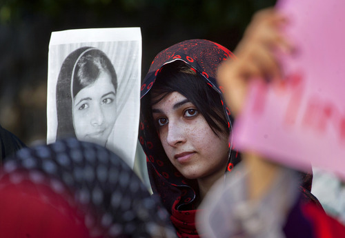 A woman supporter of a Pakistani religious group 'Minhaj-ul-Quran' holds a poster of 14-year-old schoolgirl Malala Yousufzai, who was shot on Tuesday by the Taliban, during a demonstration in Islamabad, Pakistan on Saturday, Oct. 13, 2012. Pakistan police have arrest a number of suspects in the case of Yousufzai shot and wounded by Taliban for promoting education for girls and criticizing the fundamentalist Islamic movement, officials said. (AP Photo/Anjum Naveed)