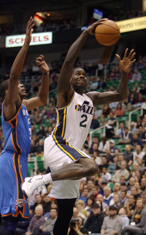 Steve Griffin | The Salt Lake Tribune   Utah's Marvin Williams leaps past the Thunder's Kevin Durant on his way to a dunk during first half action in the Jazz Thunder preseason game and EnergySolutions Arena in Salt Lake City, Utah Friday October 12, 2012.