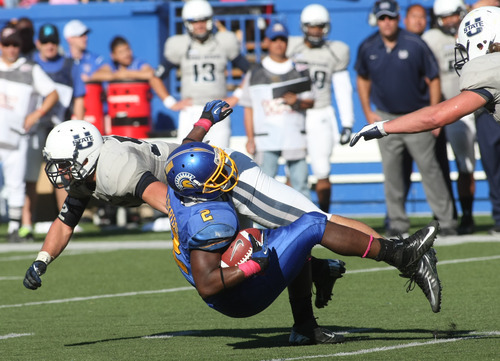 San Jose State running back De'Leon Eskridge (2) is brought down by a Utah State defender in the fourth quarter of an NCAA college football game in San Jose, Calif., Saturday, Oct. 13, 2012. Utah State defeated San Jose State 49-27. (AP Photo/Darryl Bush)