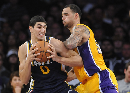 Utah Jazz center Enes Kanter (0), of Turkey, battles Los Angeles Lakers center Robert Sacre, right in the second half of an NBA preseason basketball game, Saturday, Oct. 13, 2012, in Los Angeles. The Jazz won 99-86.(AP Photo/Gus Ruelas)
