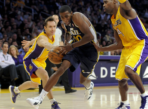 Los Angeles Lakers guard Steve Nash, left, gets his hand on the ball as Utah Jazz forward Jeremy Evans (40) attempts to get by Lakers forward Antawn Jamison (4) during the first half of an NBA preseason basketball game, Saturday, Oct. 13, 2012, in Los Angeles. The Jazz won 99-86.(AP Photo/Gus Ruelas)