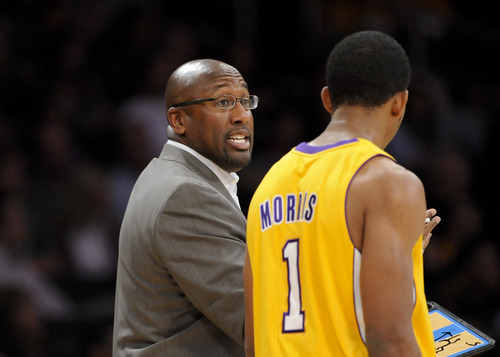 Los Angeles Lakers head coach Mike Brown, left, talks with guard Darius Morris (1) in the first half of an NBA preseason basketball game against the Utah Jazz, Saturday, Oct. 13, 2012, in Los Angeles. The Jazz won 99-86. (AP Photo/Gus Ruelas)