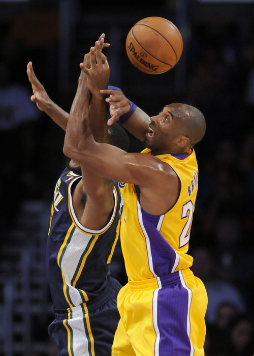 Utah Jazz forward Derrick Favors, left, and Los Angeles Lakers guard Kobe Bryant, right, fight for a loose ball in the first half of an NBA preseason basketball game, Saturday, Oct. 13, 2012, in Los Angeles. (AP Photo/Gus Ruelas)