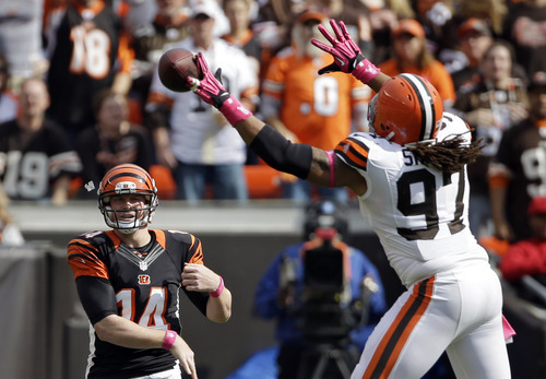 Cleveland Browns defensive end Jabaal Sheard (97) tips a pass from Cincinnati Bengals quarterback Andy Dalton (14) in the first quarter of an NFL football game Sunday, Oct. 14, 2012, in Cleveland. (AP Photo/Mark Duncan)