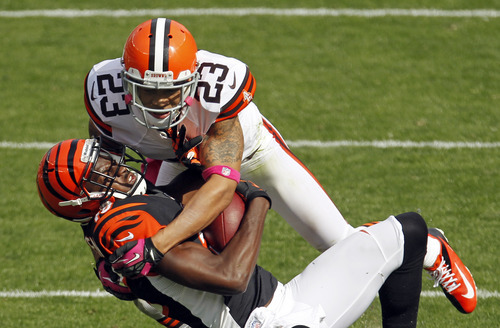 Cincinnati Bengals wide receiver A.J. Green is tackled by Cleveland Browns cornerback Joe Haden after a pass reception in the second quarter of an NFL football game Sunday, Oct. 14, 2012, in Cleveland. (AP Photo/Tony Dejak)