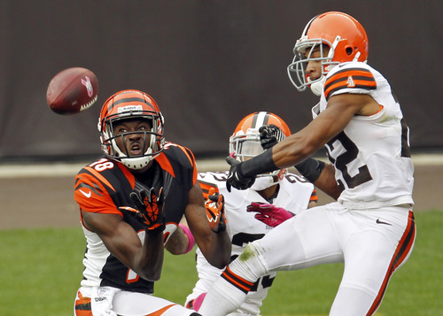 Cincinnati Bengals wide receiver A.J. Green, left, catches a pass against Cleveland Browns cornerbacks Joe Haden and Buster Skrine (22) in the second quarter of an NFL football game Sunday, Oct. 14, 2012, in Cleveland. (AP Photo/Tony Dejak)