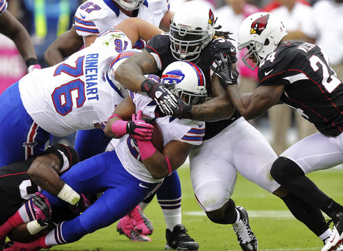 Buffalo Bills running back Fred Jackson, center, is tackled by Arizona Cardinals inside linebacker Daryl Washington, top, and Adrian Wilson (24) during the first half of an NFL football game, Sunday, Oct. 14, 2012, in Glendale, Ariz. (AP Photo/Paul Connors)