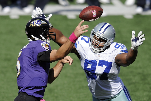 Baltimore Ravens quarterback Joe Flacco, left, throws to a receiver as he is pressured by Dallas Cowboys defensive end Jason Hatcher in the first half of an NFL football game in Baltimore, Sunday, Oct. 14, 2012. (AP Photo/Nick Wass)