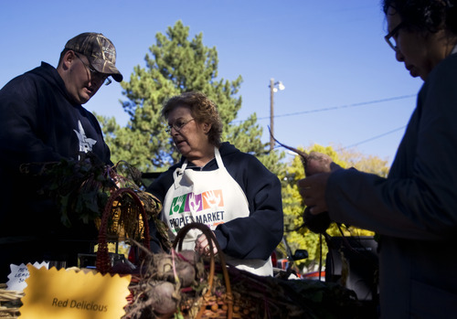 Kim Raff  |  The Salt Lake Tribune Isaac Adams and Carol Munk weigh beets for a customer at their stand at the People's Market at the International Peace Gardens in Salt Lake City on Sunday, Oct. 14, 2012.