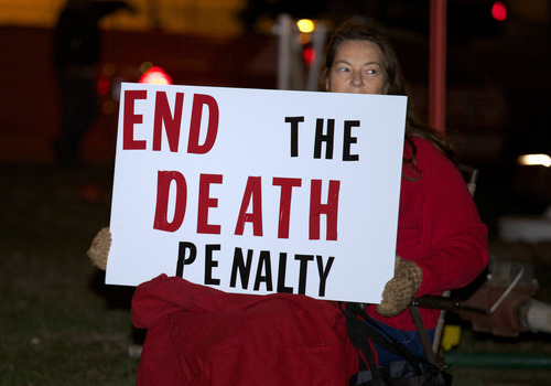 Death-penalty opponent Elaine Engelgau holds a sign during a protest outside the South Dakota Penitentiary in Sioux Falls, S.D., on Monday, Oct. 15, 2012, in anticipation of the execution of Eric Robert. Robert pleaded guilty in the April 12, 2011, slaying of a guard during a failed prison escape and asked to be put to death, saying he would kill again. He was scheduled to die by lethal injection at 10 p.m. at the State Penitentiary in Sioux Falls_ the state's first execution in five years and only the second in more than half a century. (AP Photo/Amber Hunt)