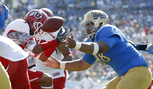 Utah wide receiver Dres Anderson, left, hauls down a deflected pass as UCLA nose tackle Seali'i Epenesa, right, heads in for the tackle for no gain at the two-yard line during the second half of their NCAA college football game, Saturday, Oct. 13, 2012, in Pasadena, Calif. UCLA won 21-14. (AP Photo/Alex Gallardo)