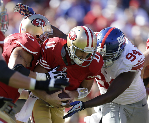 San Francisco 49ers quarterback Alex Smith (11) is sacked by New York Giants defensive tackle Linval Joseph, hidden, as outside linebacker Mathias Kiwanuka (94) converges during the third quarter of an NFL football game in San Francisco, Sunday, Oct. 14, 2012. (AP Photo/Marcio Jose Sanchez)
