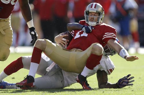 San Francisco 49ers quarterback Alex Smith (11) is sacked by New York Giants outside linebacker Mathias Kiwanuka (94) during the fourth quarter of an NFL football game in San Francisco, Sunday, Oct. 14, 2012. The Giants 26-3. (AP Photo/Marcio Jose Sanchez)
