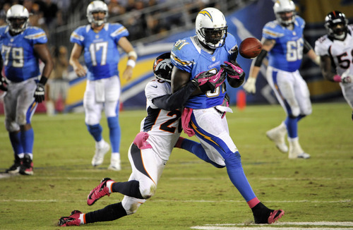 Denver Broncos strong safety Mike Adams, left, strips the ball from San Diego Chargers tight end Randy McMichael, right, during the second half of an NFL football game, Monday, Oct. 15, 2012, in San Diego. The Chargers recovered the fumble on the play. (AP Photo/Denis Poroy)