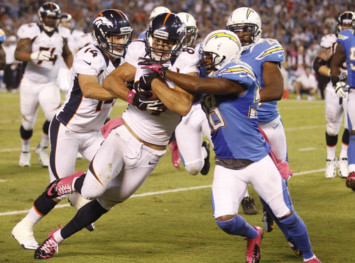 Denver Broncos wide receiver Eric Decker pushes his way towards the end zone past San Diego Chargers linebacker Demorrio Williams for the touchdown during the second half of an NFL football game Monday, Oct. 15, 2012, in San Diego. (AP Photo/Lenny Ignelzi)