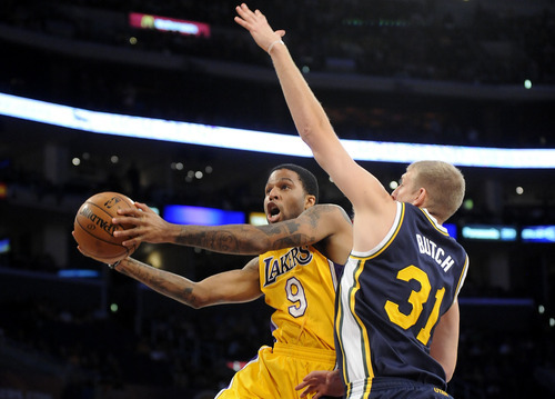 Los Angeles Lakers forward Chris Douglas-Roberts (9) drives by Utah Jazz center Brian Butch (31) for a basket in the second half of an NBA preseason basketball game, Saturday, Oct. 13, 2012, in Los Angeles. The Jazz won 99-86.(AP Photo/Gus Ruelas)