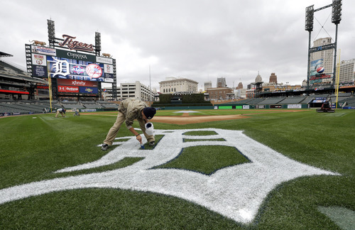 Justin DeFrancis paints the Detroit Tigers logo behind home plate at Comerica Park in Detroit, Monday, Oct. 15, 2012, to prepare for the New York Yankees in Game 3 of the American League championship series Tuesday. Detroit leads the series 2-0. (AP Photo/Paul Sancya)