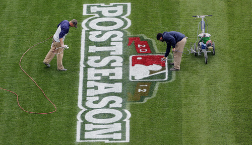 Workers paint a postseason logo on the field at Comerica Park, Monday, Oct. 15, 2012, in Detroit. The Detroit Tigers are scheduled to face the New York Yankees in Game 3 of the American League championship series Tuesday. Detroit leads the series 2-0. (AP Photo/Charlie Riedel)