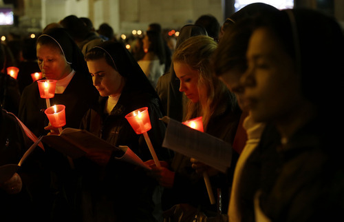 Faithful pray during a candlelight procession to mark the 50th anniversary of the Second Vatican Council - the church meetings that modernized the Catholic Church but whose true results are still hotly debated - in St. Peter's square, at the Vatican, Thursday, Oct. 11, 2012. Pope Benedict XVI denounced the