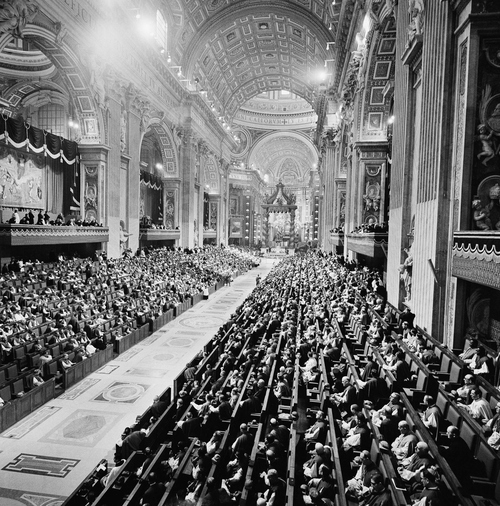 This is an overhead general view of the central nave of St. Peter's Basilica in Vatican City, Dec. 8, 1962, during the closing ceremonies of the Roman Catholic Church's Ecumenical Council's first phase.  The Council Fathers are sitting in their stands at left and right, and the galleries above are crowded with observer-delegates and prominent guests.  (AP Photo/Jim Pringle)