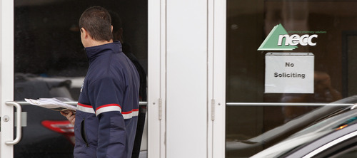 FILE - In a Thursday, Oct. 4, 2012 file photo, a delivery man walks up to the door of New England Compounding in Framingham, Mass. Federal and state investigators have been tightlipped about any problems they may have seen at the pharmacy whose steroid medication has been linked to a lethal outbreak of a rare fungal form of meningitis, or whether they have pinpointed the source of the contamination. They did disclose Thursday, Oct. 11, 2012 that they found fungus in more than 50 vials from the company. (AP Photo/Stephan Savoia, File)