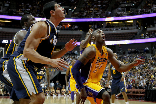 Los Angeles Lakers' Kobe Bryant, right, and Utah Jazz's Enes Kanter look at the ball in the first half of an NBA preseason basketball game in Anaheim, Calif., Tuesday, Oct. 16, 2012. (AP Photo/Jae Hong)