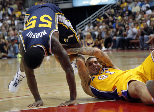 Los Angeles Lakers' Reeves Nelson, right, and Utah Jazz's Kevin Murphy fight for the ball during the first half of an NBA preseason basketball game in Anaheim, Calif., Tuesday, Oct. 16, 2012. (AP Photo/Jae Hong)
