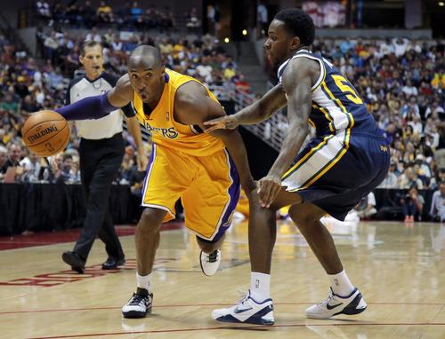 Los Angeles Lakers' Kobe Bryant, left, is pressured by Utah Jazz's Kevin Murphy during the first half of an NBA preseason basketball game in Anaheim, Calif., Tuesday, Oct. 16, 2012. (AP Photo/Jae Hong)