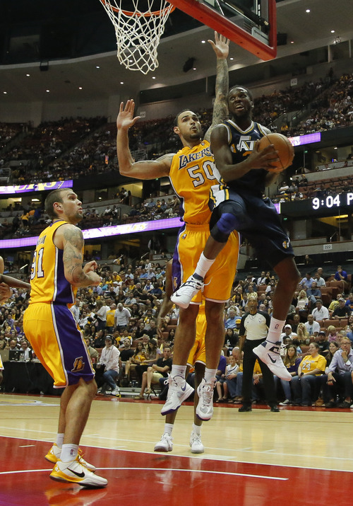 Utah Jazz's DeMarre Carroll, right, goes up for a basket against Los Angeles Lakers' Robert Sacre in the second half of an NBA preseason basketball game in Anaheim, Calif., Tuesday, Oct. 16, 2012. The Jazz won 114-80. (AP Photo/Jae Hong)