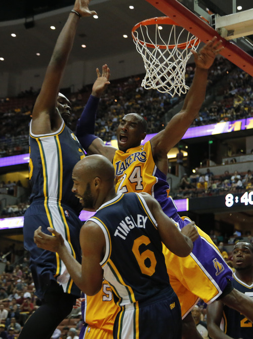 Los Angeles Lakers' Kobe Bryant, center, is fouled by Utah Jazz's Jamaal Tinsley, foreground, in the second half of an NBA preseason basketball game in Anaheim, Calif., Tuesday, Oct. 16, 2012. The Jazz won 114-80. (AP Photo/Jae Hong)