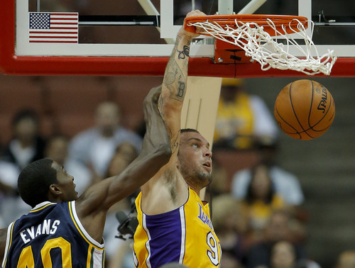 Los Angeles Lakers' Reeves Nelson, center, dunks against Utah Jazz's Jeremy Evans in the second half of an NBA preseason basketball game in Anaheim, Calif., Tuesday, Oct. 16, 2012. The Jazz won 114-80. (AP Photo/Jae Hong)