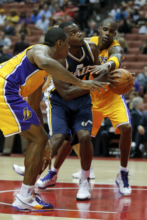 Utah Jazz's Paul Millsap, center, looks to shoot as he is defended by Los Angeles Lakers' Metta World Peace, left, and Antawn Jamison during the first half of an NBA preseason basketball game in Anaheim, Calif., Tuesday, Oct. 16, 2012. (AP Photo/Jae Hong)