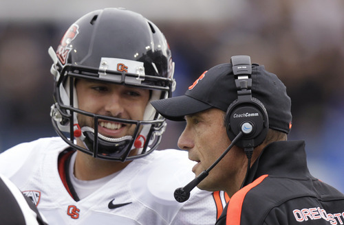Oregon State coach Mike Riley talks with quarterback Cody Vaz during the first quarter of an NCAA college football game with Brigham Young on Saturday, Oct. 13, 2012, in Provo, Utah. (AP Photo/Rick Bowmer)