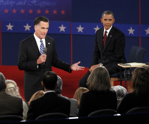 President Barack Obama, right, listens as Republican presidential candidate former Massachusetts Gov. Mitt Romney answers a question from a member of the audience during the second presidential debate at Hofstra University, Tuesday, Oct. 16, 2012 in Hempstead, N.Y.  (AP Photo/Mary Altaffer)