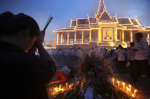 Mourners burn incense and offer prayers at the Royal Palace displaying a portrait of their late King Norodom Sihanouk in Phnom Penh, Cambodia, Wednesday Oct. 17, 2012. The body of Sihanouk returned to his homeland on a plane from China on Wednesday, welcomed by tens of thousands of mourners who packed tree-lined roads in the Southeast Asian nation's capital ahead of the royal funeral. (AP Photo/Wong Maye-E)