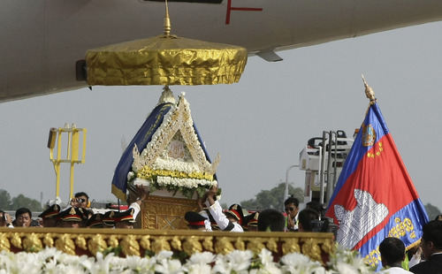 Police officers carry a casket carrying the body of Cambodia's late King Norodom Sihanouk upon arrival at Phnom Penh International Airport in Phnom Penh, Cambodia, Wednesday, Oct. 17, 2012. The body returned to his homeland on a plane from China on Wednesday, welcomed by tens of thousands of mourners who packed tree-lined roads in the Southeast Asian nation's capital ahead of the royal funeral. (AP Photo/Heng Sinith)
