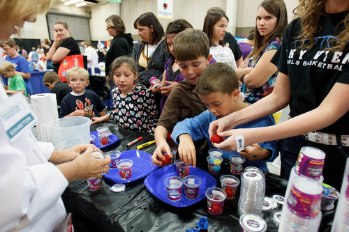 Trent Nelson  |  The Salt Lake Tribune Meg Buonforte of Mad Science of Greater Salt Lake helps children make rubber bouncing balls through a chemical reaction at the Utah Education Association (UEA) convention on Thursday in Sandy.