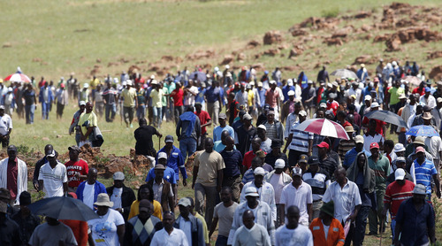 Miners assemble on a hill during their strike at the AngloGold Ashanti Mine in Fochville near Johannesburg, South Africa, Thursday, Oct. 18, 2012. Strike action in gold and platinum mines had cost the country about 4.5 billion rand (more than $500 million) in lost output by mid-September, President Zuma told a meeting of businessmen in Johannesburg last week. (AP Photo/Themba Hadebe)