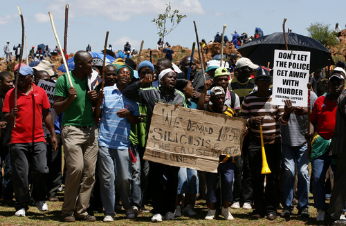 Miners sing during their strike at the AngloGold Ashanti Mine in Fochville near Johannesburg, South Africa, Thursday, Oct. 18, 2012. Strike action in gold and platinum mines had cost the country about 4.5 billion rand (more than $500 million) in lost output by mid-September, President  Zuma told a meeting of businessmen in Johannesburg last week. (AP Photo/Themba Hadebe)
