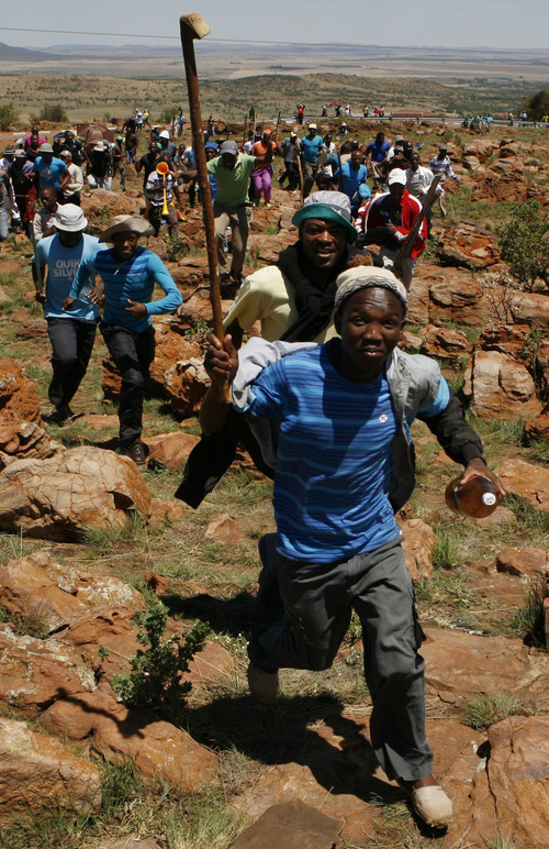 Miners sing as they run during their strike at the AngloGold Ashanti Mine in Fochville near Johannesburg, South Africa, Thursday, Oct. 18, 2012. Strike action in gold and platinum mines had cost the country about 4.5 billion rand (more than $500 million) in lost output by mid-September, President Zuma told a meeting of businessmen in Johannesburg last week. (AP Photo/Themba Hadebe)