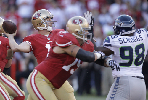 San Francisco 49ers quarterback Alex Smith (11) passes as offensive tackle Alex Boone (75) blocks Seattle Seahawks defensive end Greg Scruggs (98) during the first quarter of an NFL football game in San Francisco, Thursday, Oct. 18, 2012. (AP Photo/Ben Margot)