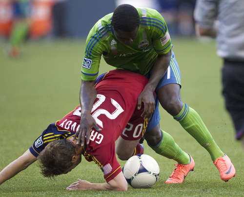 The Sounders' Eddie Johnson, top, falls on top of Real Salt Lake's Ned Grabavoy during the first half of play in a MLS soccer match, Saturday, May 12, 2012, in Seattle. (AP PHOTO/Stephen Brashear)