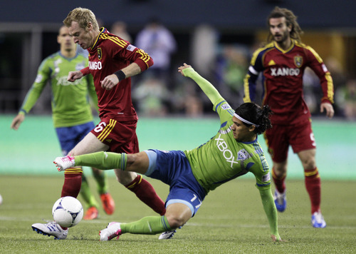 Seattle Sounders' Fredy Montero (17) comes in from the side to challenge Real Salt Lake's Nat Borchers (6) for the ball in the first half of an MLS soccer match, Wednesday, Oct. 17, 2012, in Seattle. (AP Photo/Ted S. Warren)