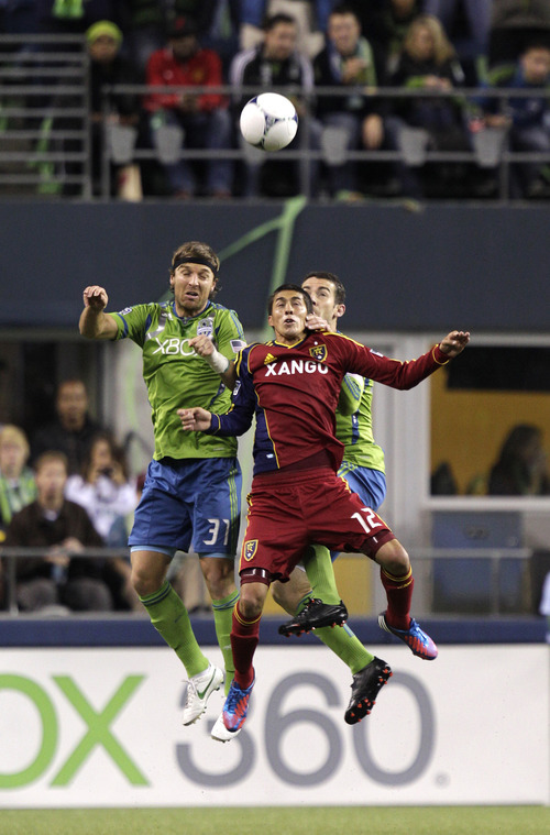 Real Salt Lake's Emiliano Bonfigli (12) goes up for a header against Seattle Sounders' Jeff Parke, left, and Zach Scott during the first half of an MLS soccer match, Wednesday, Oct. 17, 2012, in Seattle. (AP Photo/Ted S. Warren)
