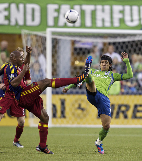Real Salt Lake's Jamison Olave, left, and the Sounders' Fredy Montero battle for the ball during the second half of play in a MLS soccer match, Saturday, May 12, 2012, in Seattle. Real Salt Lake won the match 1-0. (AP PHOTO/Stephen Brashear)